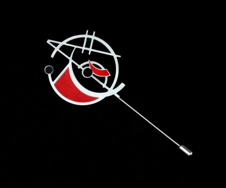 Pasador plateado de aguja con fornitura abstracta de formas geométricas vaciadas y troqueladas en una única pieza con engastes de papel rubí y negro.