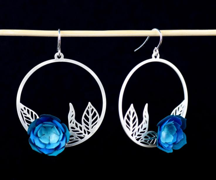 Two camelia earrings, with a circular base and carved leaves inside with a layered blue paper flower and silver clasps.