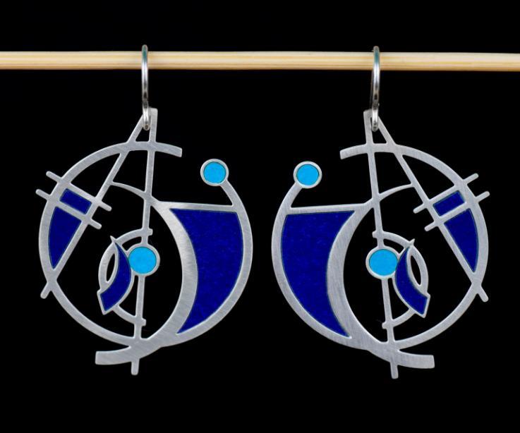 Pendientes plateados de base circular abierta con diseño geométrico de formas abstractas y secciones con engastes de papel azul con cierres de gancho.