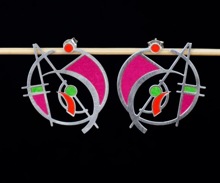 Plano frontal de pendientes de aro plateados con formas geométricas superpuestas rematadas con vivos de papel de tonos lila, verde y rojo semi brillo.