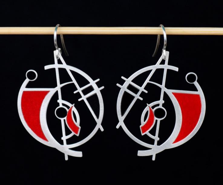 Zarcillos plateados y semi circulares con diseño geométrico de formas abstractas y secciones con engastes de papel rojo rematados en cierres de gancho.
