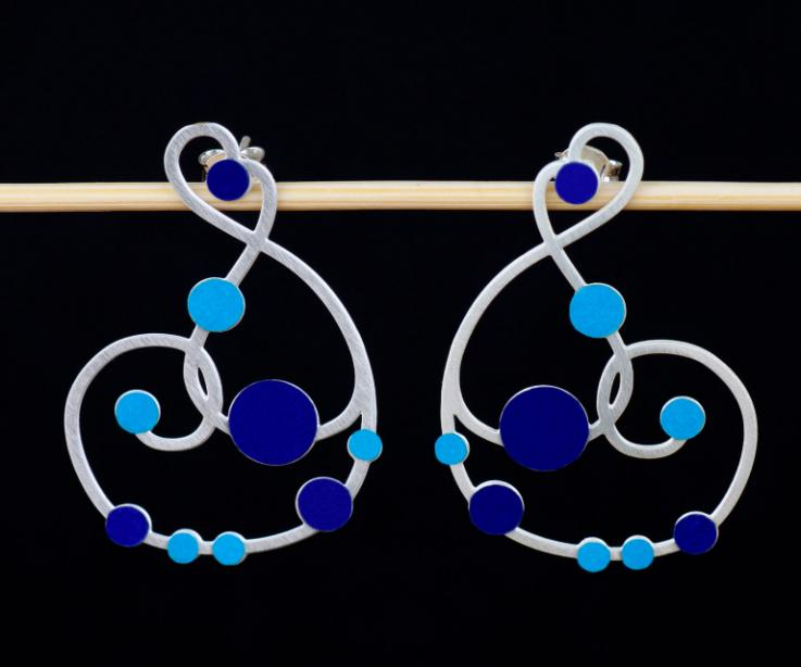 Vista frontal de un par de pendientes plateados con cierre de tuerca y diseño sinuoso recorrido con incrustaciones de círculos de papel en tonos azules.