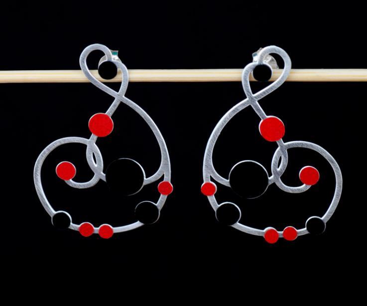Plano frontal de un par de pendientes plateados con cierre de tuerca y diseño sinuoso recorrido con incrustaciones de círculos de papel rojo y negro.