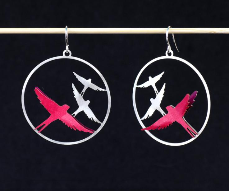 Front view of two silver hoop earrings, with a flat flock of filigree and two 3D birds embedded in layers of pink paper with a glossy finish.