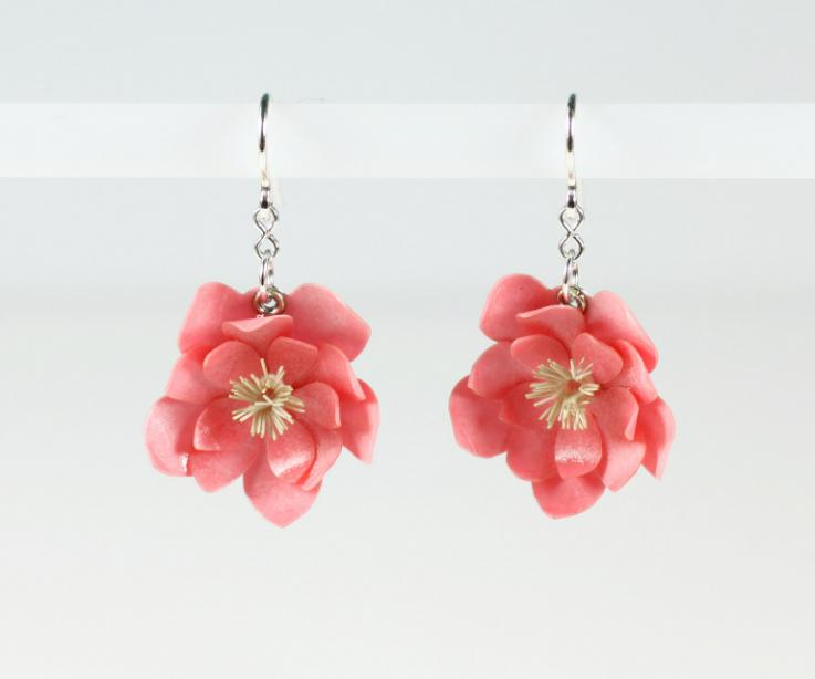Long earrings topped with a pink flower set in sterling silver