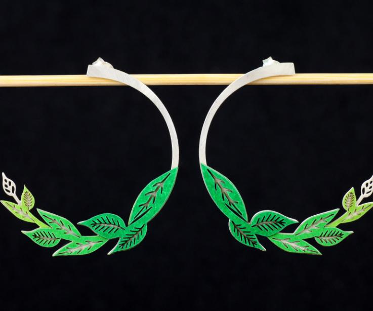 Front view of two silver-plated earrings, with a hidden silver clasp and carved sections, set with green paper leaves.