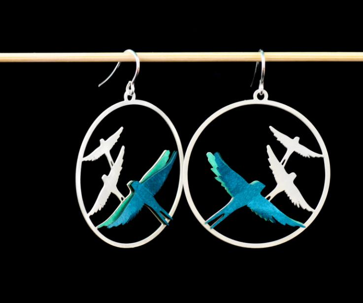 Frontal shot of two hoop earrings with sterling silver attachments, carved birds and paper-layered birds in blue-green.
