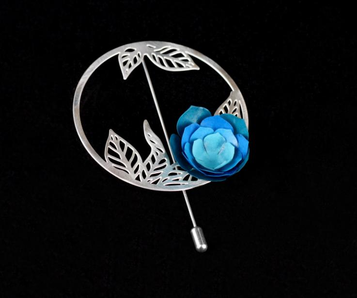 Silver brooch with a camellia, circular base and die-cut leaves inside with a blue paper flower and a needle fastener.