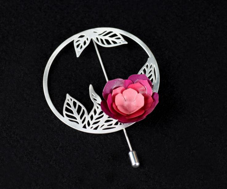 Camellia brooch with a circular base, needle clasp and small carved leaves inside, with a paper petal flower in pink tones.
