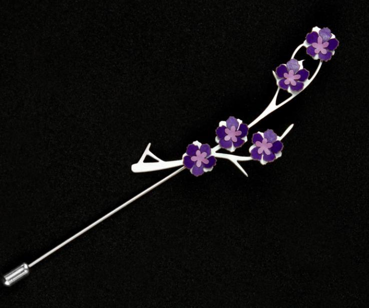 Prendedor de aguja con base plateada de ramas de metal tallado con pequeños engastes de flores tridimensionales de papel en tonos coordinados de morado.