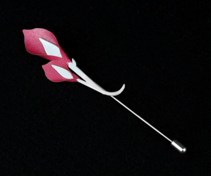 Silver needle pin with a design of two pink paper lilies and two branches interlaced and carved into a single piece that serves as a base.