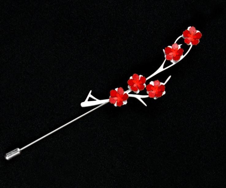 Plano frontal de un prendedor de aguja plateado con base de ramas talladas e incrustaciones de flores rojas de papel modelado con acabado semi brillo.