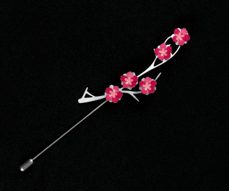 Prendedor plateado con cierre de aguja, base con elegante ramaje de metal y engastes de flores de papel rosa endurecido y con un acabado semi brillo.