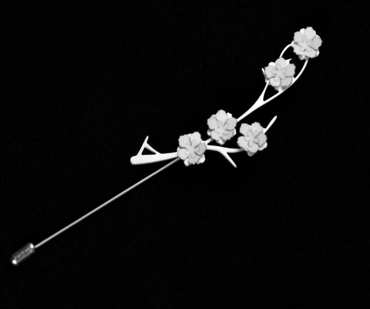 Vista frontal de un prendedor de agujón con una base de pequeñas ramas talladas e incrustaciones de flores blancas de papel modelado y acabado brillo.