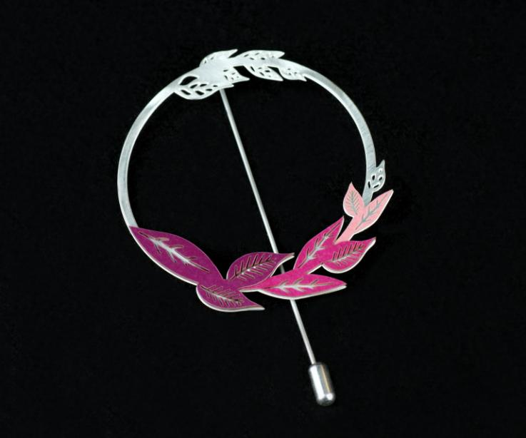 Front view of a circular silver brooch with a pinhole, small leaves carved in the same piece and paper leaves in pink and purple tones.