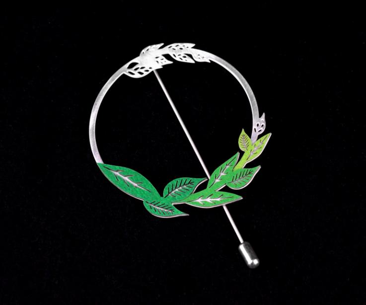 Front view of a needle brooch with silver circular base, with an elegant branching and die-cutting of green paper leaves, partially set.