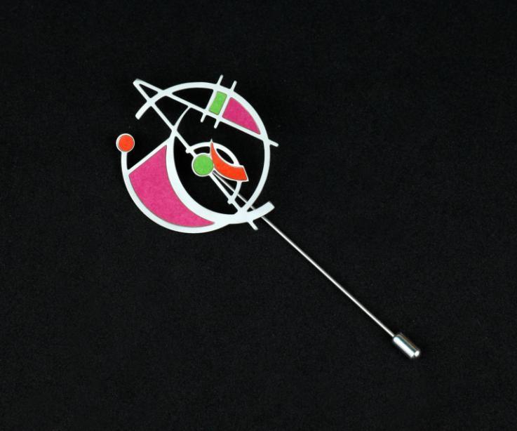 Plano frontal de un prendedor de aguja con diseño de base circular, figuras geométricas vaciadas y engastes de papel de colores púrpura, verde y rubí.