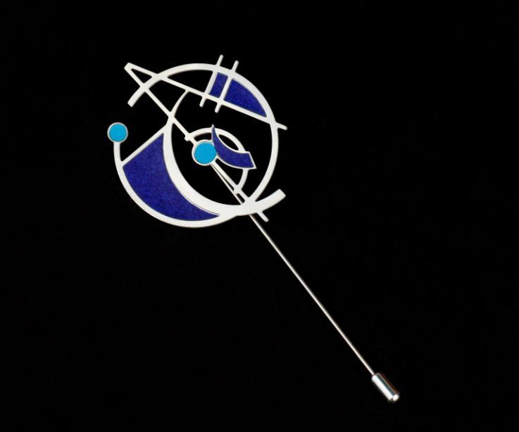 Pasador de agujón y diseño geométrico con figuras vaciadas en una única estructura semi circular plateada con incrustaciones de papel de tonos azules.