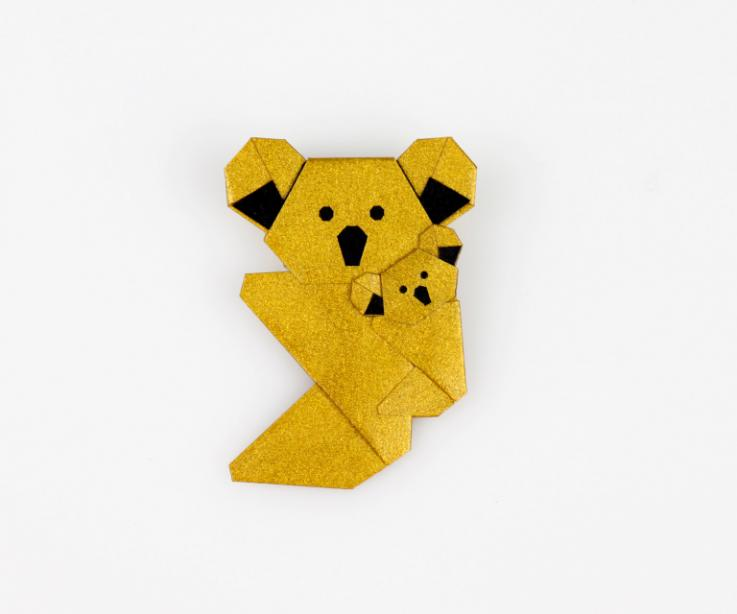Vista frontal de un broche realizado con un koala de origami en color dorado con toques metalizados con una pequeña cría a cuestas.