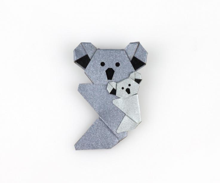 Vista frontal de un broche con imperdible de una simpática pareja de koalas de papel endurecido en colores grises.