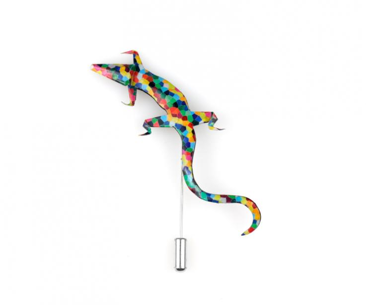 Vista frontal de un agujón con forma de salamandra realizado en papel endurecido y resistente al agua decorado con mosaicos de colores.