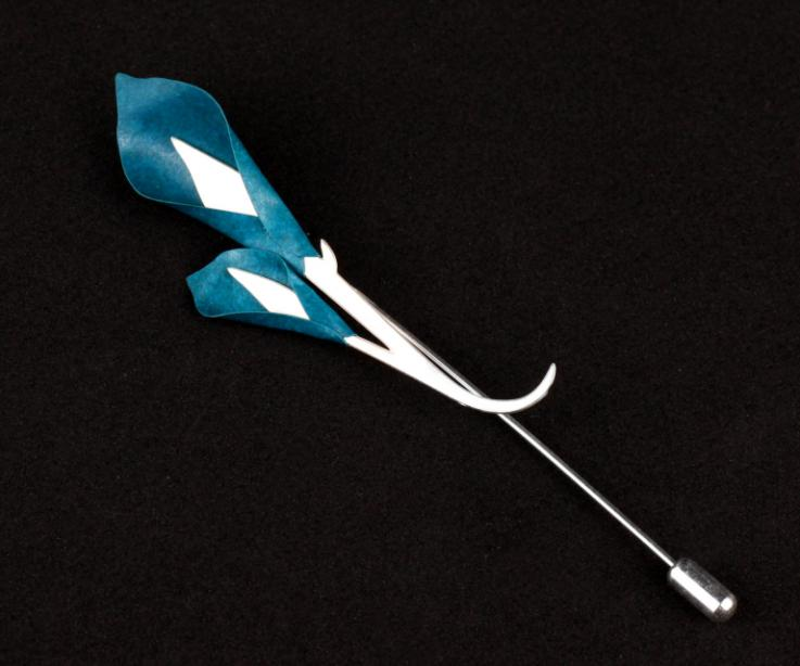 Pasador plateado con dos incrustaciones de flores de calas de papel de color azul y ramas  entrelazadas y talladas en la base con cierre de aguja.
