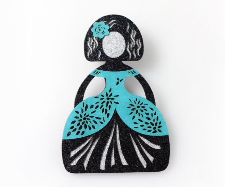 Broche realizado por la superposición de capas de papel con forma de menina con vestido de color azul