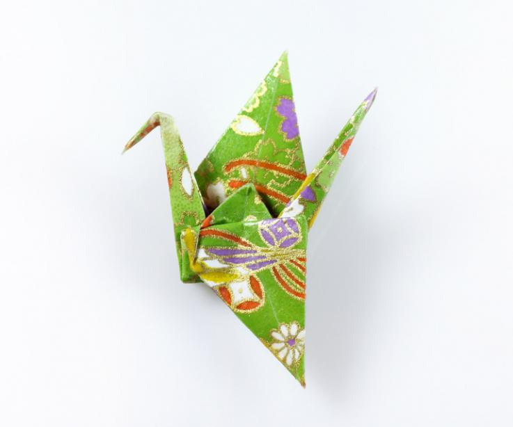 Youthful origami brooch with paper crane, front view