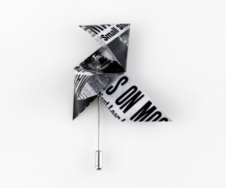 Plano frontal con fondo blanco de un broche de aguja con una original pajarita 3D de papel ilustrado con páginas de periódicos de estética Mid Century.