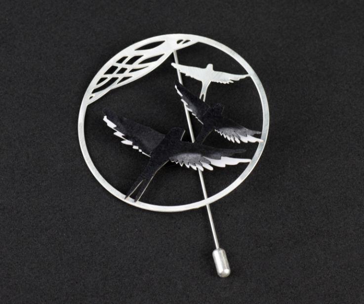 Vista frontal de un prendedor de aro con agujón, vaciado con siluetas de pájaros talladas y piezas de papel negro modeladas y engastadas con efecto 3D.