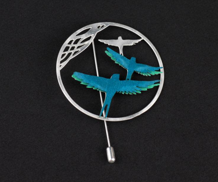 Vista detalle de un broche con dos pájaros de papel de color turquesa engastados en una base circular tallada con filigrana y cierre de agujón.