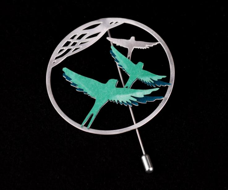 Front view of filigree ring pin and green paper birds with spread wings, inlaid and modeled with 3D effect.
