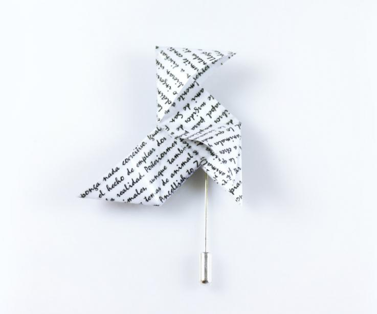 Juvenile paper origami bird clasp with letters, front view