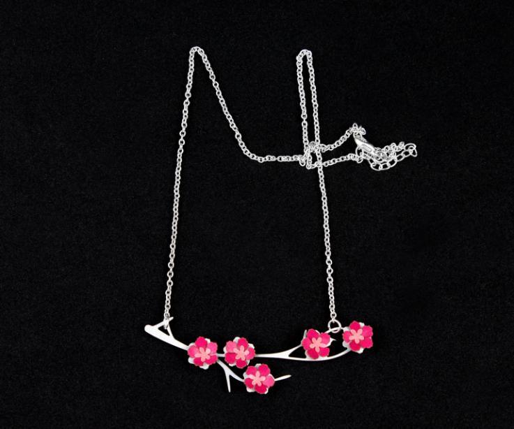 Original choker con colgante de rama plateada, flores de almendro en papel rosa engastadas y elegante cadena de eslabones plateada sobre fondo negro.