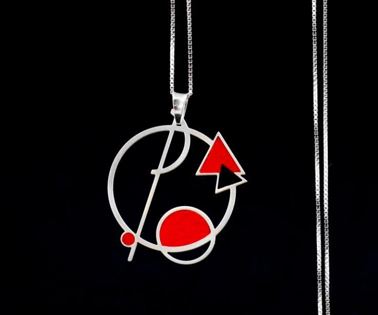 Primer plano de colgante circular atravesado por una línea, círculos pequeños y triángulos con vivos de papel en color carmín y cadena fina de plata.