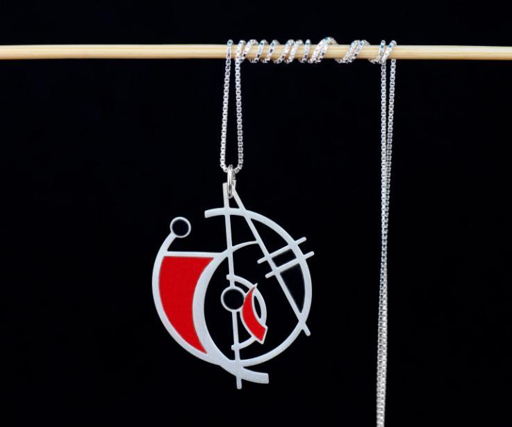 Plano frontal de un colgante circular atravesado por líneas y figuras irregulares con vivos de papel en color carmín y negro rematado en cadena fina.