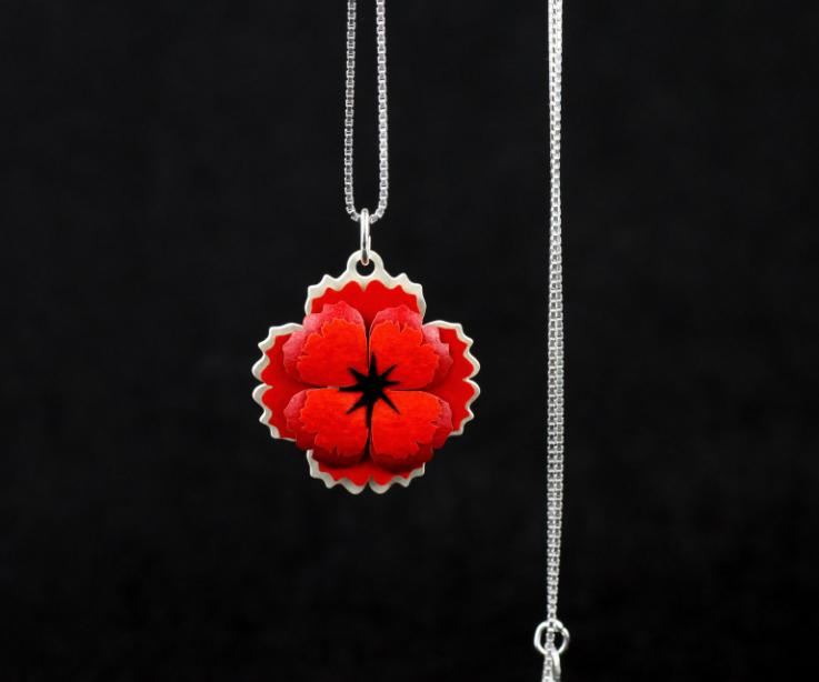 Close-up of a pendant with poppy with carmine paper petals, embedded in a die-cut base and attached to a sterling silver chain.