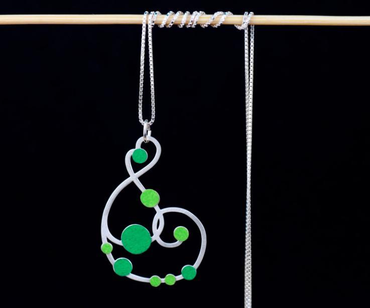 Vista frontal de un collar largo plateado con cadena veneciana y colgante de formas sinuosas embellecido con pequeños círculos de papel de color verde.
