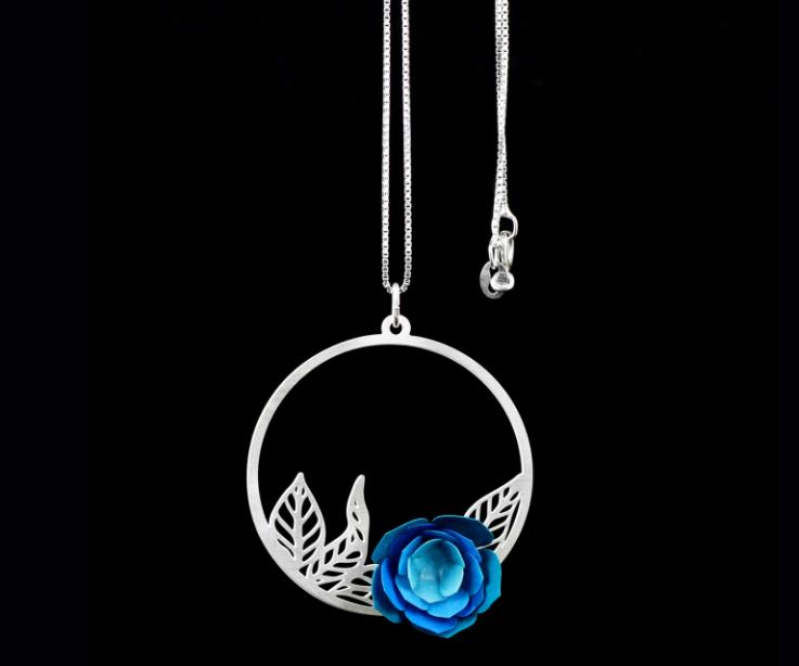 Close-up of blue paper camellia flower pendant mounted on an artistic hoop with leaf filigree that is attached to a sterling silver chain.