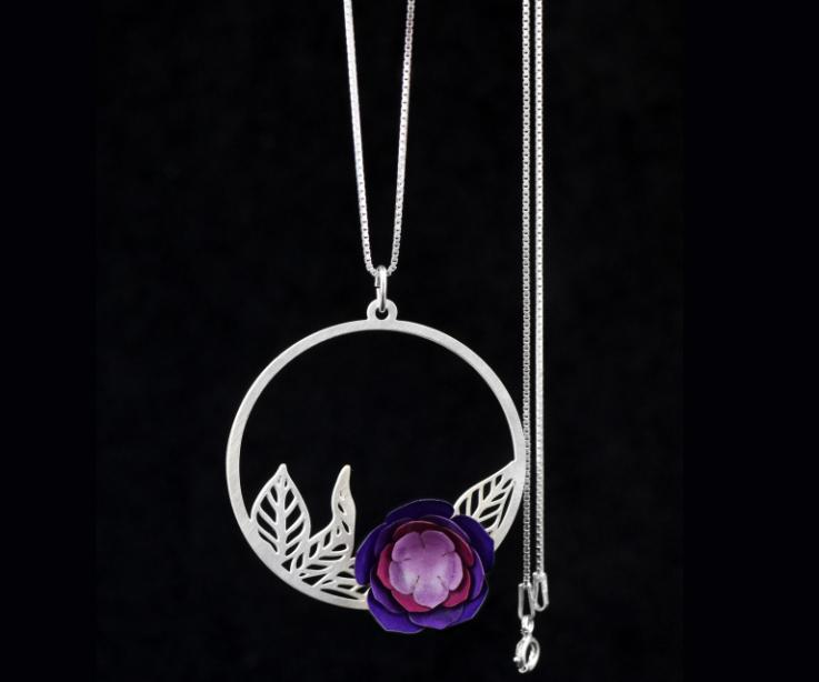 Sterling silver chain with a circular pendant of carved leaves inside and a handmade camellia flower in hard paper with violet tones.
