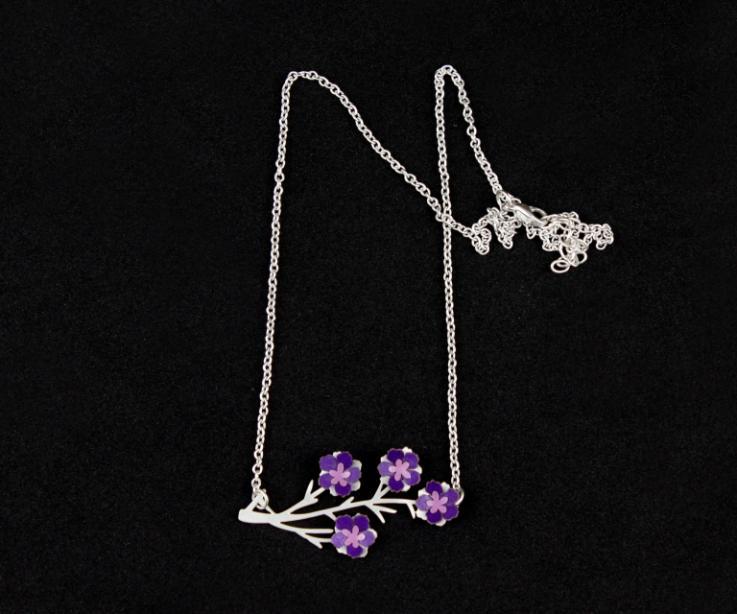 Primer plano de un colgante con flores de papel modeladas en color morado montadas en una base de ramas talladas, con cadena de eslabones de plata.