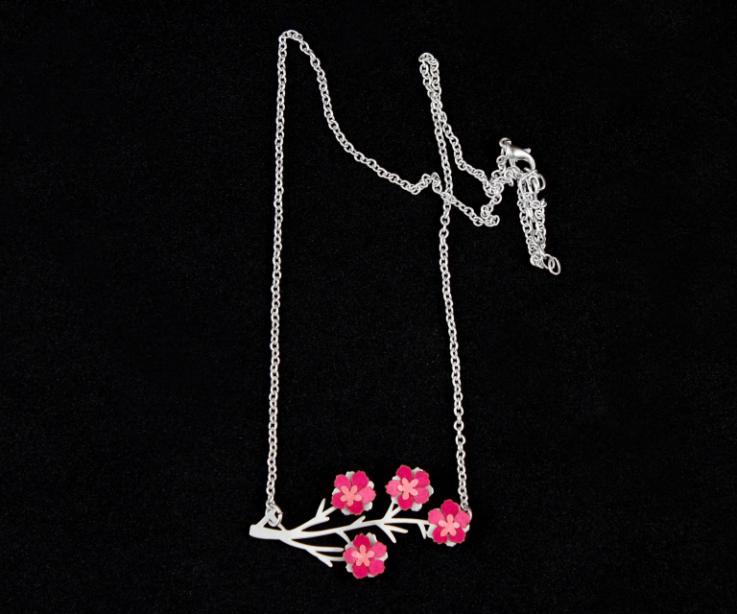 Original collar con un dije de ramas troqueladas, flores de almendro en papel rosa engastadas y elegante cadena de eslabones en plata sobre fondo negro.