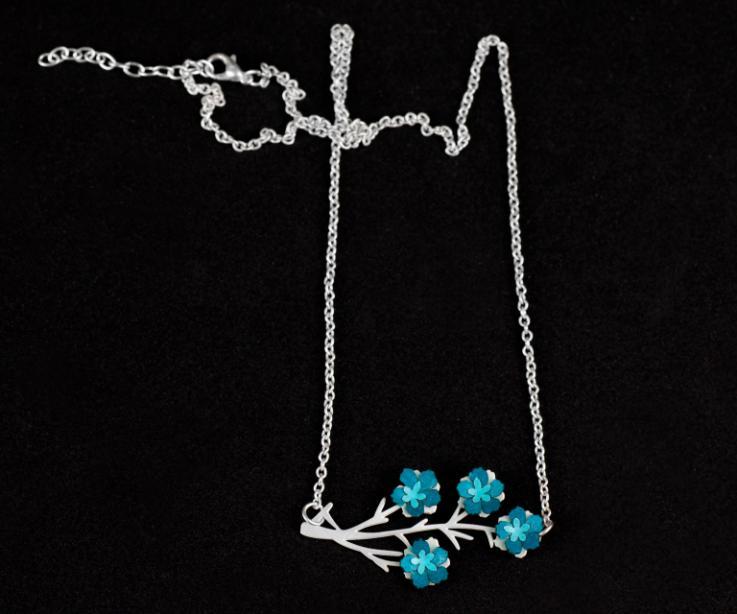 Primer plano de un collar con cadena de plata de ley y cuatro pequeñas flores de papel de tonos azules engastadas en una elegante base de ramas troquelada.