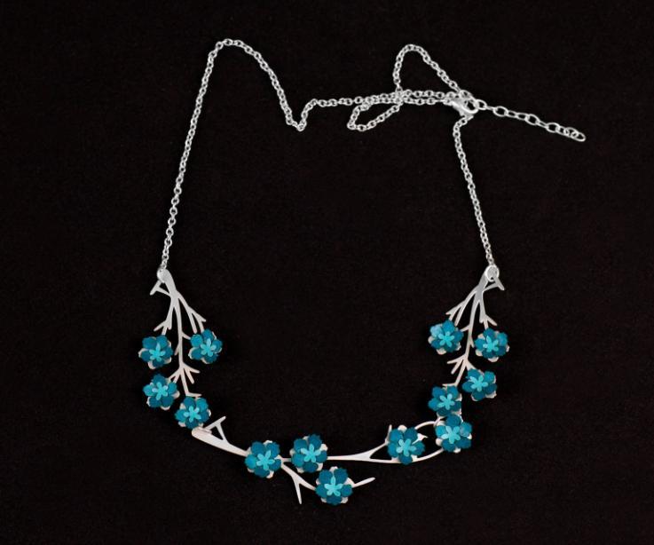 Vista frontal de un hermoso collar plateado con cadena de eslabones, ramas de metal y originales engastes de florecillas de papel en tonos azulados.