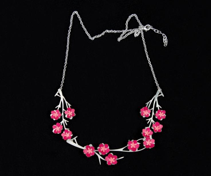 Plano frontal de colgante plateado con pequeñas flores de papel rosa de acabado semi brillo sobre una elegante base móvil de ramas troqueladas.