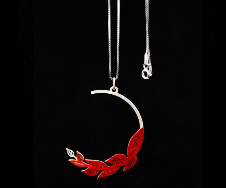 Detail view of pendant with carmine paper leaves mounted on a truncated hoop with carved foliage sections and a silver Venetian chain.
