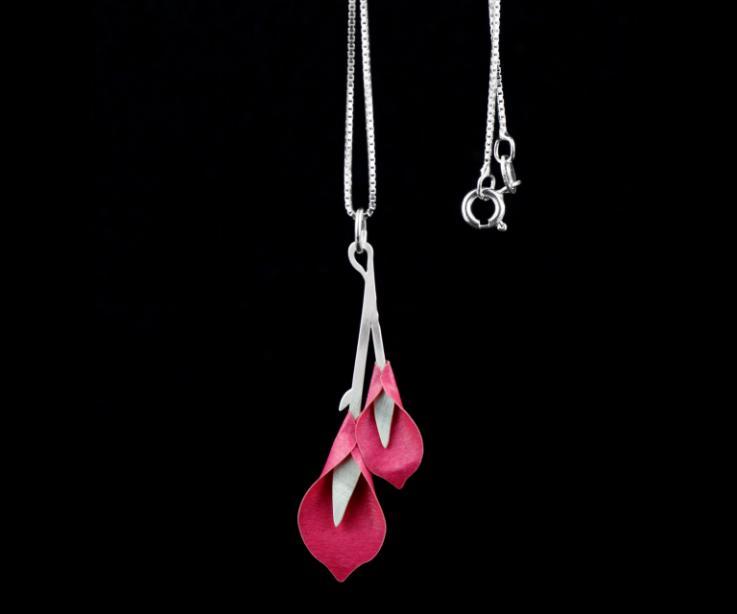 Plano detalle de colgante con flores de lillium modeladas en papel de color rosa brillo que se engarzan en una cadena veneciana de plata de ley.