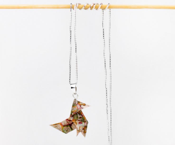 Vista frontal de un colgante con pajarita de origami volumétrica, ilustrada con mapamundi y engastado en una elegante cadena de plata de ley tipo veneciana.