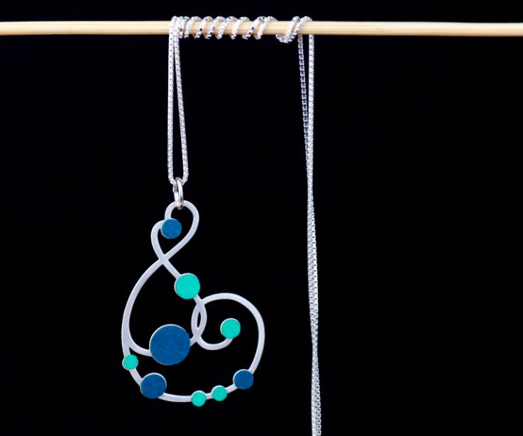 Vista frontal de collar largo plateado con cadena fina y un hermoso colgante de diseño sinuoso embellecido con engarces de papel en tonos aguamarina.