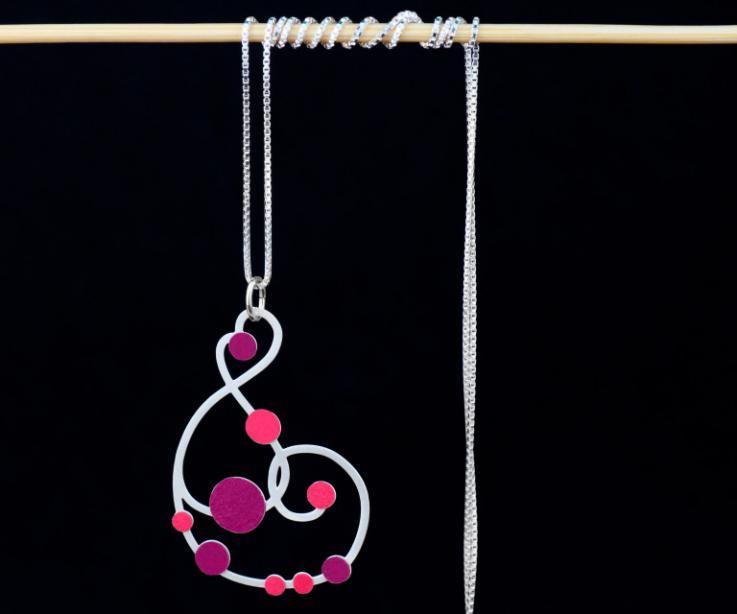 Vista frontal de un collar plateado formado por cadena fina y un hermoso colgante de formas sinuosas embellecido con engarces de papel en tonos malva.